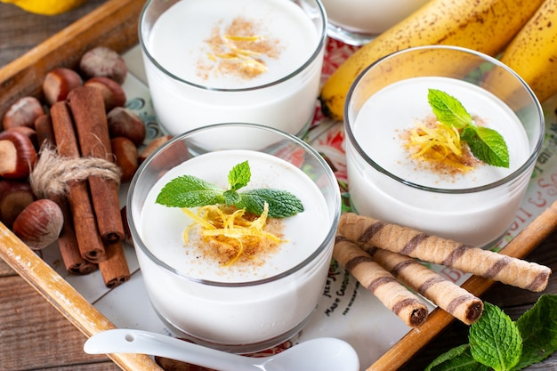 Fresh banana yogurt with oats in glass, delicious dessert for healthy breakfast