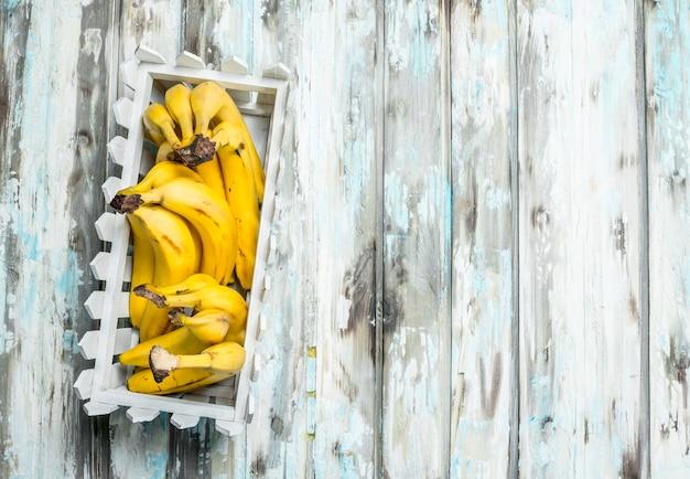 白いプラスチックのバスケットに入った新鮮なバナナ。白い木製の背景に。