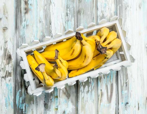 Свежие бананы в белой пластиковой корзине.