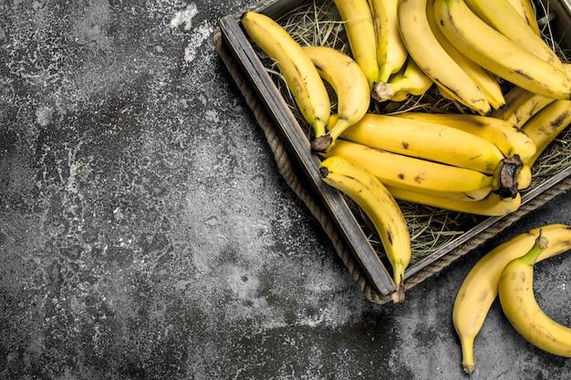古い箱に入った新鮮なバナナ。素朴な背景に。