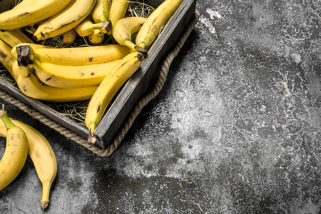 Fresh bananas in an old box. on a rustic background.