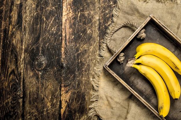 古いトレイに新鮮なバナナ。木製の背景に。