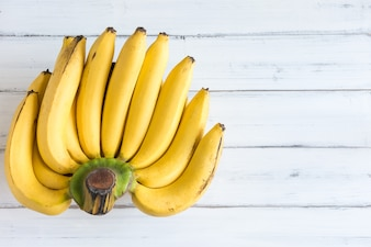 Fresh bananas on white wooden background