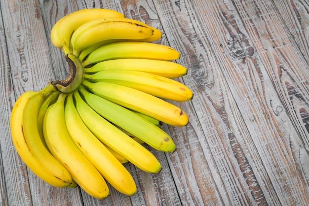 木製のテーブルの上に新鮮なバナナ。