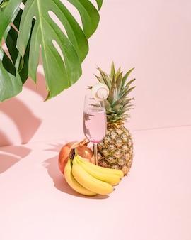 パステルピンクの背景にガラスの新鮮なバナナ、パイナップル、ザクロ、リフレッシュメントジュース。自然な緑の植物の影。夏の熱帯のシーン。