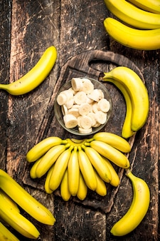 木製のテーブルの上にボウルに刻んだ断片と新鮮なバナナ