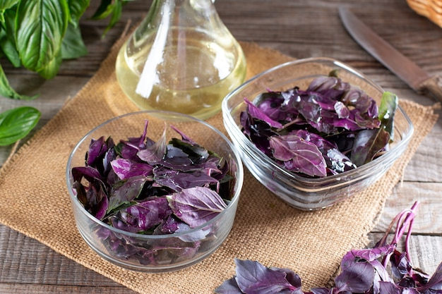 Свежие листья базилика в контейнере с оливковым маслом на деревянном столе. концепция здорового питания.
