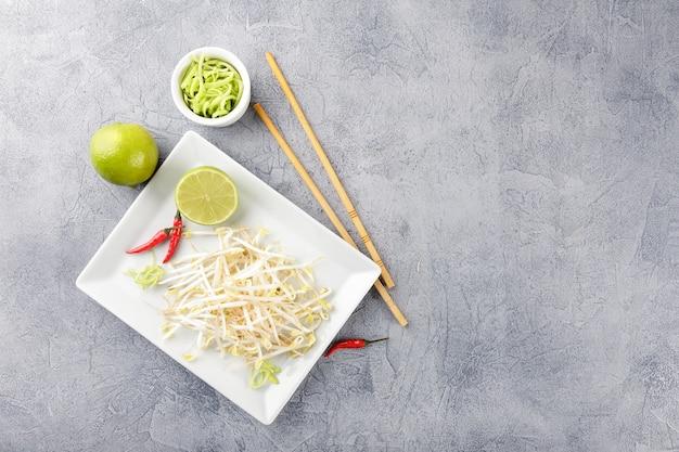 Ростки свежей фасоли на белой квадратной тарелке и палочках для еды. концепция здорового питания, вегетарианской пищи. вид сверху