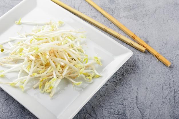 Ростки свежей фасоли на белой квадратной тарелке и палочках для еды. концепция здорового питания, вегетарианской пищи.