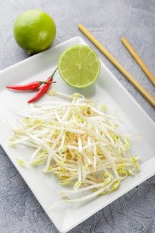 Fresh bean sprouts on white square plate and chopsticks. concept of healthy foods, vegetarian food.