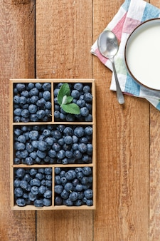 Fresh beautiful blueberries in wooden box and cup of milk on wooden table. top view