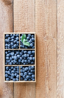 Fresh beautiful blueberries in wooden box on wooden table. top view