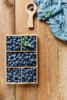 Fresh beautiful blueberries in wooden box on wooden table