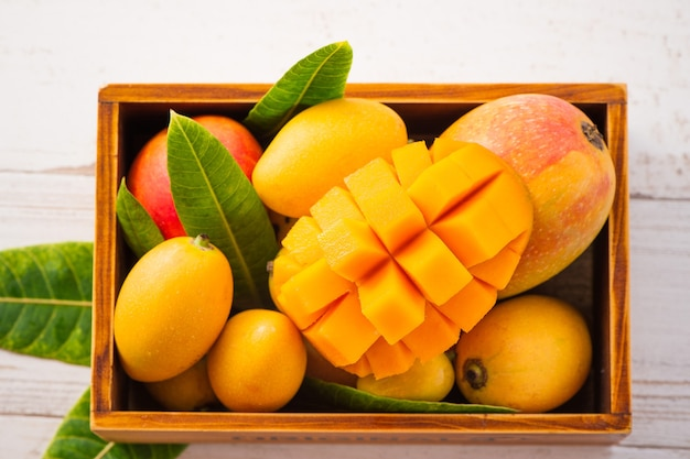 Fresh and beautiful mango fruit set in a wooden box with sliced diced mango chunks on a light wooden background, copy space(text space), blank for text