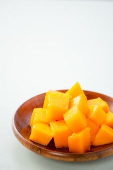 Fresh and beautiful mango fruit with sliced diced mango chunks on a light blue background, copy space(text space), blank for text.
