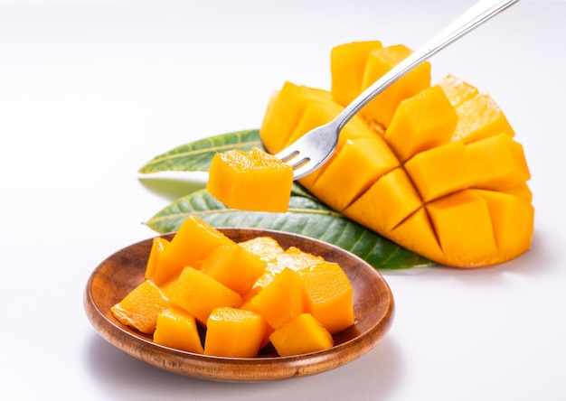 Fresh and beautiful mango in a wooden plate with sliced diced mango chunks isolated with white background, copy space(text space), blank for text