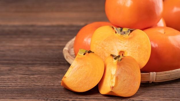 暗い木製のテーブルの上の竹のふるいに新鮮で美しいオレンジ色の柿柿。中国の旧正月の季節の伝統的な果物、クローズアップ。
