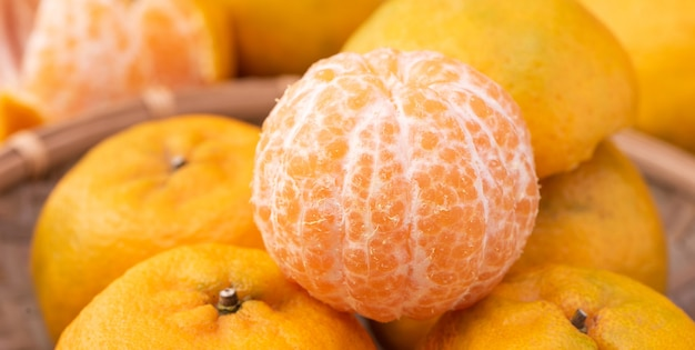 暗い木製のテーブルの上の竹のふるいに新鮮で美しいオレンジ色のタンジェリン。中国の旧正月の季節の伝統的な果物、クローズアップ。 Premium写真