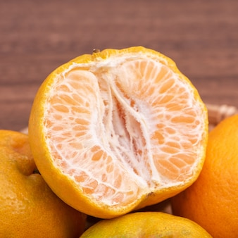 暗い木製のテーブルの上の竹のふるいに新鮮で美しいオレンジ色のタンジェリン。中国の旧正月の季節の伝統的な果物、クローズアップ。