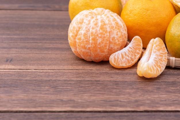Свежий, красивый мандарин оранжевого цвета на бамбуковом сите над темным деревянным столом. сезонные, традиционные фрукты китайского лунного нового года, крупным планом.