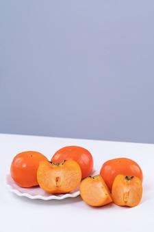 グレーブルーの背景、中国の旧正月のデザインコンセプト、白いキッチンテーブルに分離された新鮮な美しいスライスした甘い柿カキをクローズアップ。