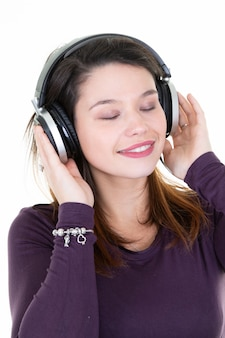 Fresh beautiful young brunette woman with closed eyes with dj headphones posing