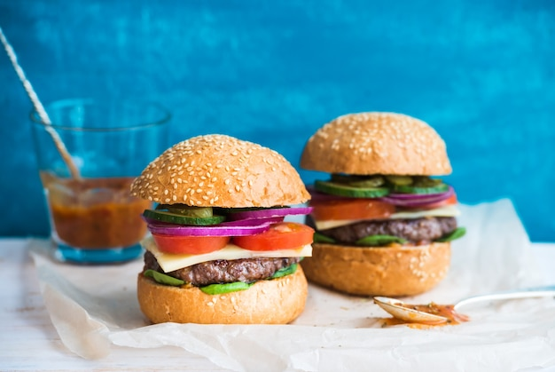 Fresh beef burger with cheese, vegetables and spicy tomato sauce on paper, blue wooden .