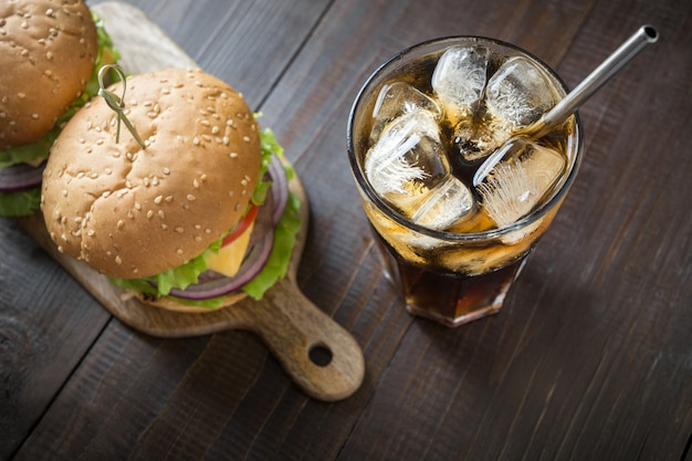 Fresh beef burger with cola on wooden board