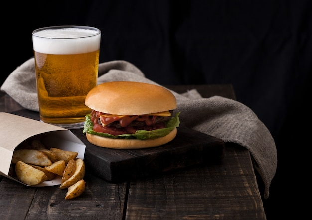 Fresh beef burger with potato wedges and glass of beer on wooden background