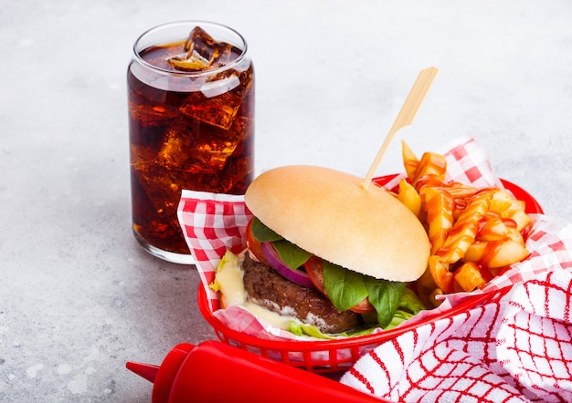 Fresh beef burger with sauce and vegetables and glass of cola soft drink with potato chips fries in red serving basket on stone kitchen.