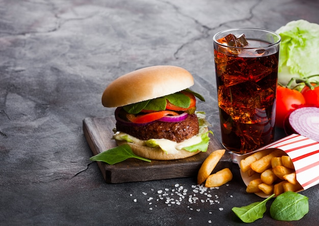 Fresh beef burger with sauce and vegetables and glass of cola soft drink with potato chips fries on stone kitchen.