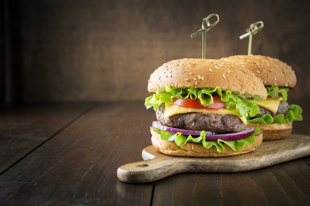 Fresh beef burger with vegetables on wooden board