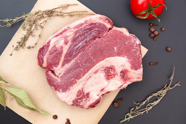 Свежее мясо говядины в окружении специй. крафт-бумага на черном камне, оформление бакалеи, оформление тимьян, розмарин, черный перец, мясо. сырой стейк из говядины на деревянной разделочной доске с травами и специями.