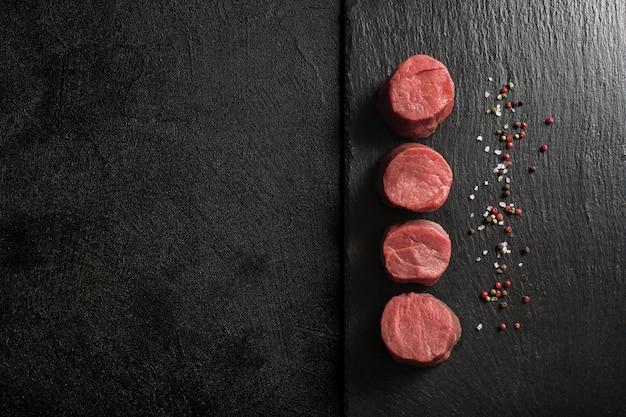 Медальоны из свежей говядины на кухонной разделочной доске