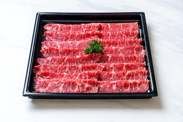 すき焼きとしゃぶまたは焼肉に使用する、霜降りのテクスチャーでスライスした新鮮な牛肉