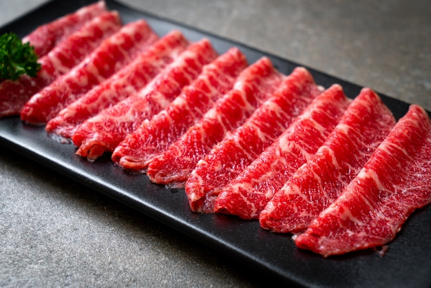 Свежая сырая говядина, нарезанная мраморной текстурой, подается к сукияки и шабу или якинику