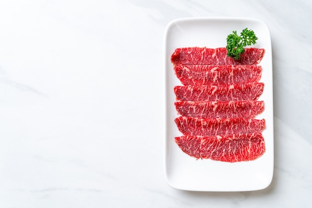 すき焼きとしゃぶしゃぶまたは焼肉に使用される大理石のテクスチャーでスライスされた新鮮な牛肉