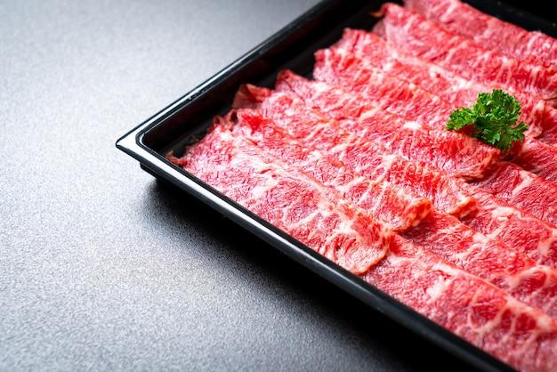 すき焼きとしゃぶまたは焼肉にマーブルテクスチャーでスライスした新鮮な牛肉