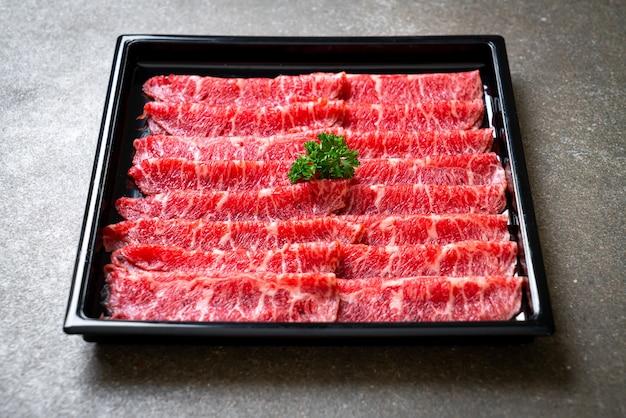Fresh beef raw sliced with marbled texture served for sukiyaki and shabu or yakiniku