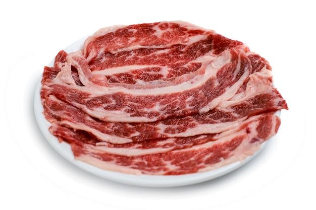 Кусочек свежей говядины на черной тарелке, изолированные на белом фоне