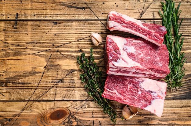 정육점 나무 테이블에 신선한 쇠고기 짧은 갈비. 나무 배경입니다. 평면도. 공간을 복사합니다.