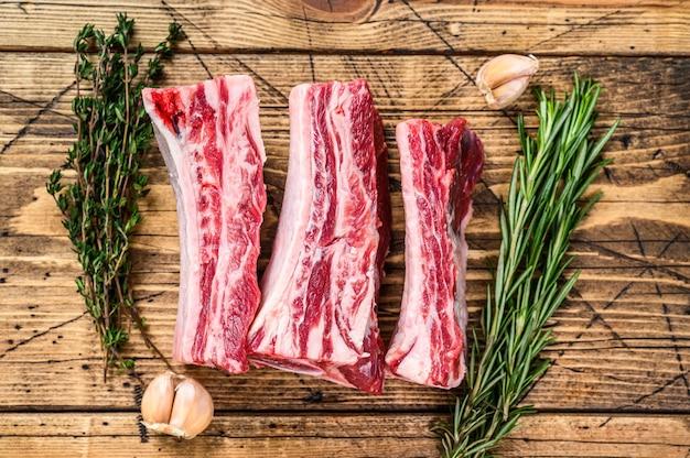 정육점 나무 테이블에 신선한 쇠고기 갈비. 나무 배경입니다. 평면도.