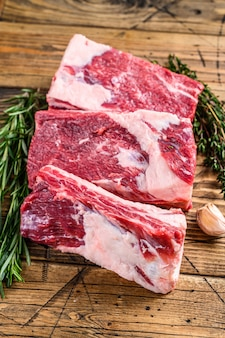 정육점 나무 테이블에 신선한 쇠고기 짧은 갈비. 나무 배경입니다. 평면도.