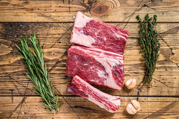 Короткие ребрышки свежей говядины на деревянном столе мясника