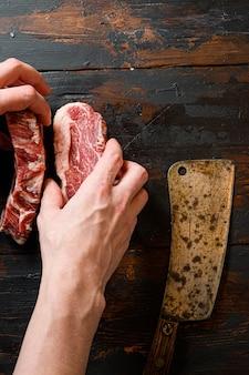 Свежий стейк из говядины руками мясника и ножом для мяса за работой