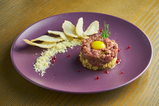 Fresh beef tartar with capers, sawn egg yolk and parmesan cheese. delicious appetizer.