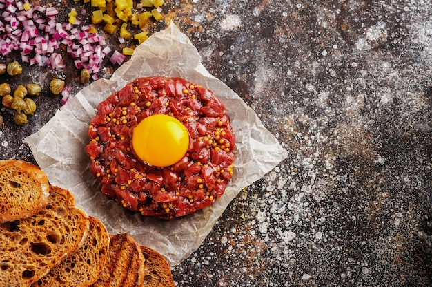 Fresh beef tartare with yolk, capers, onions and mustard, top view. flat lay.