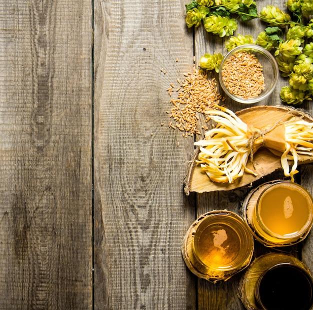 木製のテーブルに新鮮なビールと塩味のチーズ。上面図