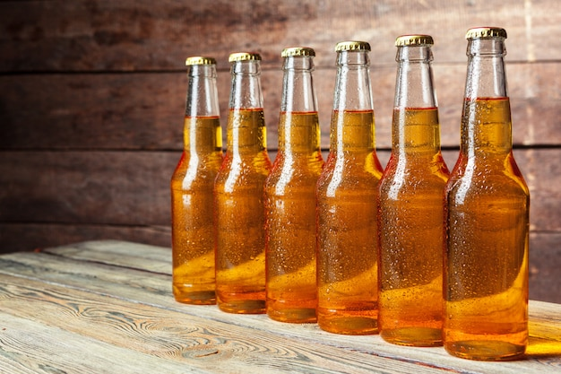 Fresh beer in glass bottles on wooden