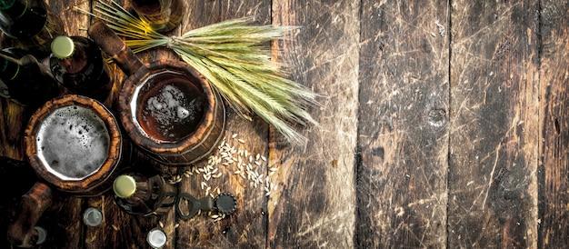 木製の背景に木製マグカップで新鮮なビール
